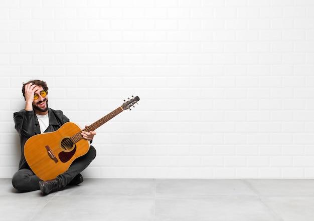 """Młody muzyk śmiejący się i uderzający w czoło, jakby mówił """"och! zapomniałem, albo to był głupi błąd z koncepcją gitary, rock and rolla"""