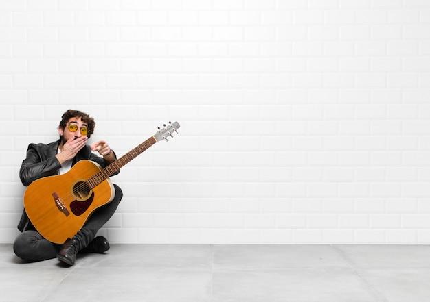 Młody muzyk śmieje się z ciebie i kpi z ciebie lub kpi z koncepcją gitary, rock and rolla
