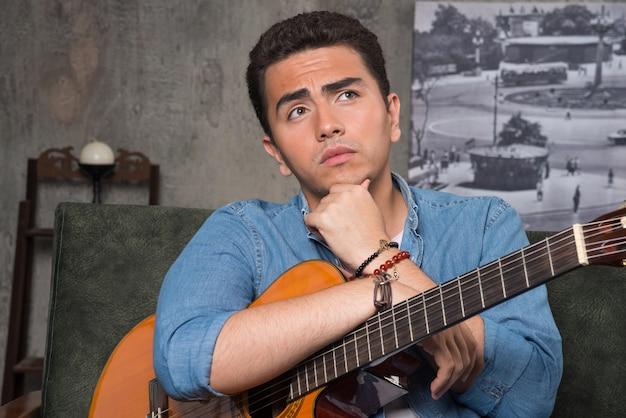 Młody muzyk trzymając piękną gitarę i siedząc na kanapie