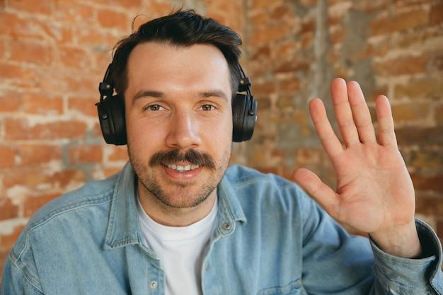 Młody muzyk w słuchawkach wita publiczność przed koncertem online lub próbą dźwięku w domu