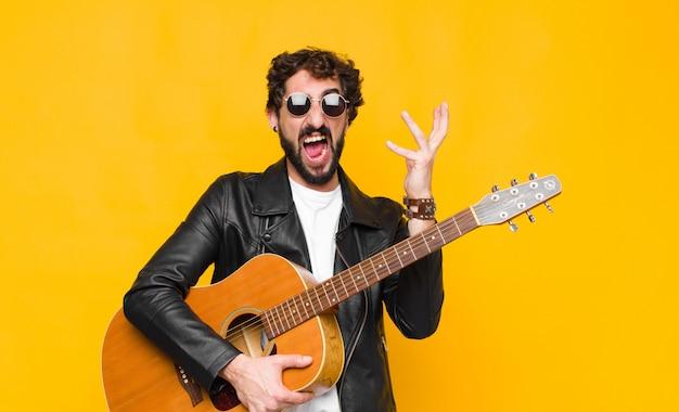 Młody muzyk wściekle krzyczy, czuje się zestresowany i zirytowany rękami w powietrzu mówiąc, dlaczego ja z koncepcją gitary, rock and rolla