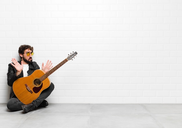 Młody muzyk wyglądający na zdenerwowanego, niespokojnego i zaniepokojonego, mówiąc, że to nie moja wina, albo nie zrobiłem tego z koncepcją gitary, rock and rolla