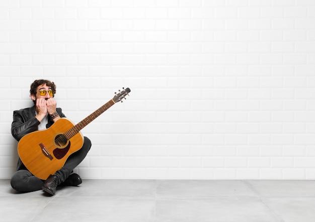 Młody muzyk wyglądający na zmartwionego, niespokojnego, zestresowanego i przestraszonego, gryzącego paznokcie i szukającego bocznego skopiowania przestrzeni z koncepcją gitary, rock and rolla