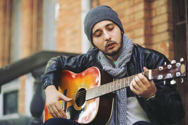 Młody muzyk z gitarą w mieście