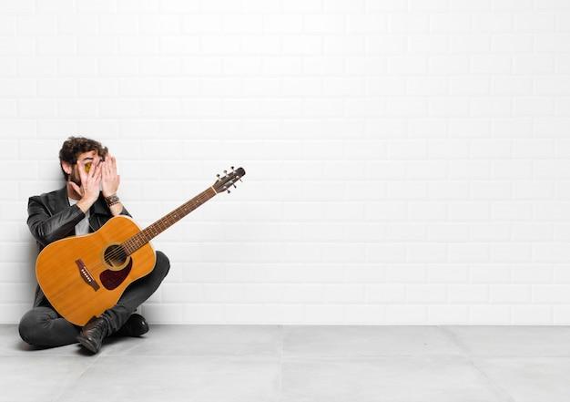 Młody muzyk zakrywający twarz rękami, zaglądający między palcami ze zdziwionym wyrazem twarzy i patrzący na gitarę