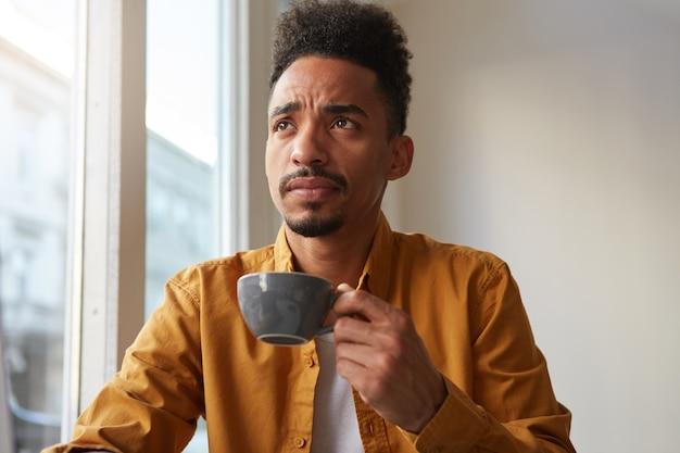Młody myślący afroamerykanin nosi żółtą koszulę, siedzi przy stoliku w kawiarni i pije aromatyczną kawę, trochę zdenerwowany. patrząc w zamyśleniu w dal.