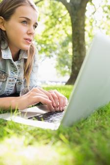 Młody myślący studencki lying on the beach na trawie używać jej laptop