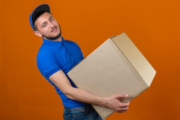 Młody nad napięte dostawy mężczyzna ubrany w niebieską koszulkę polo i czapkę stojącą z pudełkiem patrząc zmęczony na pojedyncze pomarańczowe tło