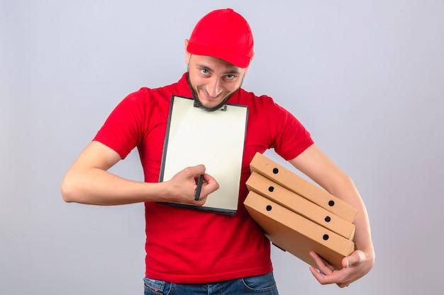 Młody, nadwyrężony mężczyzna dostawy ubrany w czerwoną koszulkę polo i czapkę ze stosem pudełek po pizzy trzymający schowek z prośbą o podpis na białym tle