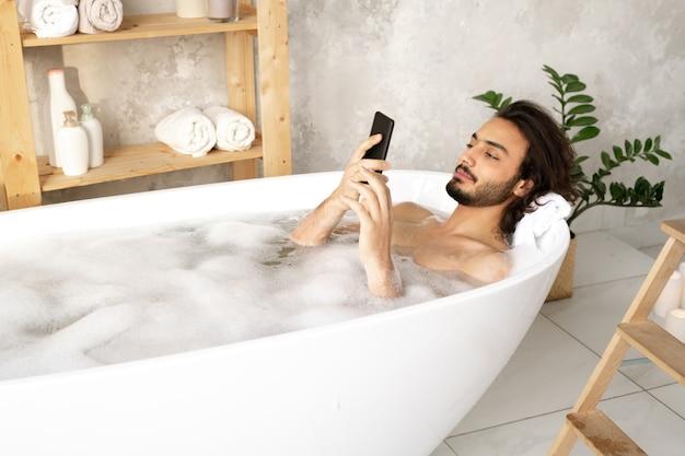 Młody nagi mężczyzna ogląda wideo lub przewija w smartfonie, leżąc w wannie wypełnionej wodą i pianą w łazience