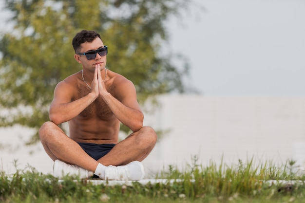 Młody nagi mężczyzna w okularach przeciwsłonecznych i białych tenisówkach siedzi na drewnianej podłodze na ulicy ze skrzyżowanymi nogami.
