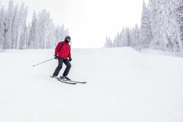 Młody narciarz w ruchu w górskim ośrodku narciarskim z pięknym zimowym krajobrazem