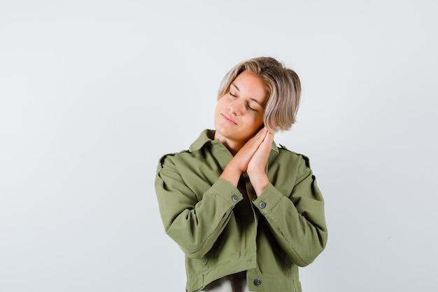 Młody nastolatek chłopak opierając się na dłoniach jako poduszka w zielonej kurtce i patrząc zrelaksowany. przedni widok.