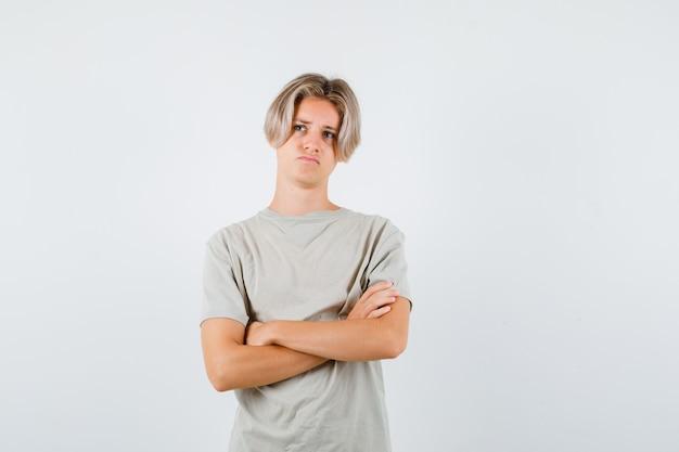 Młody nastolatek chłopak stojący ze skrzyżowanymi rękami, patrzący w t-shirt i patrzący zdesperowany. przedni widok.