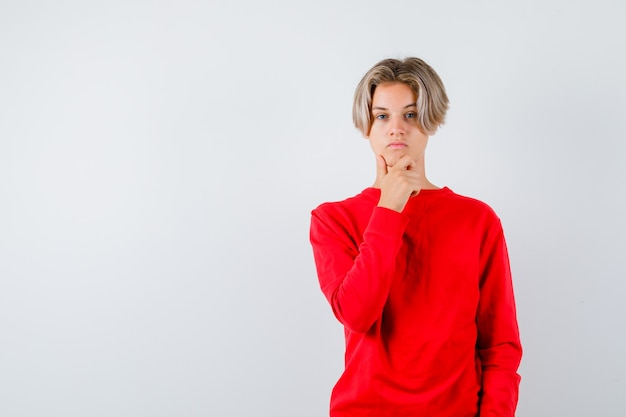 Młody nastolatek chłopak w czerwonym swetrze z ręką na brodzie i patrząc zamyślony, widok z przodu.