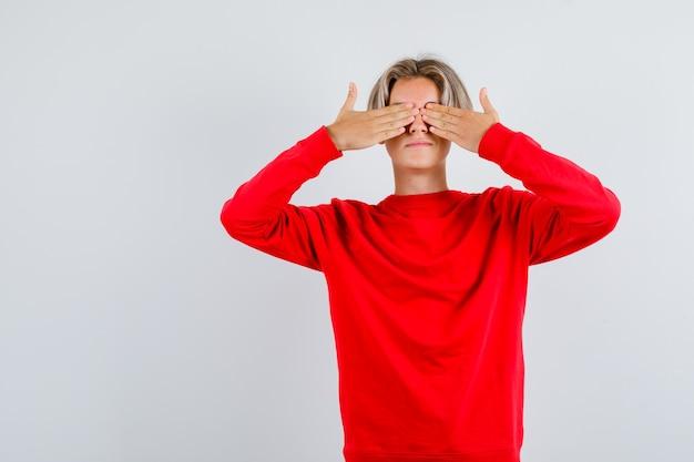 Młody nastolatek chłopak w czerwonym swetrze z rękami na oczach i patrząc podekscytowany, widok z przodu.