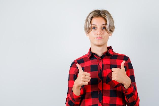 Młody nastolatek chłopak w kraciastej koszuli pokazując podwójne kciuki w górę i patrząc zadowolony, widok z przodu.