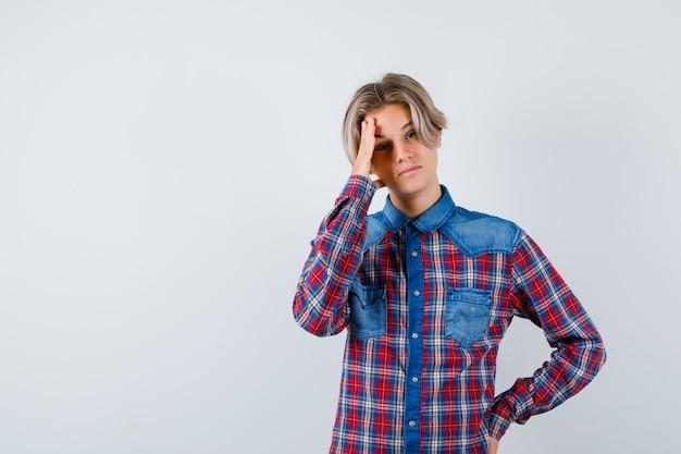 Młody nastolatek chłopiec cierpiący na ból głowy w kraciastej koszuli i wyglądający na zakłopotanego. przedni widok.
