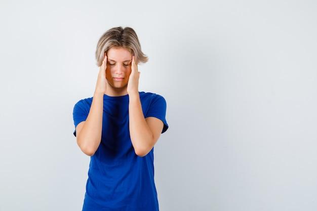 Młody nastolatek chłopiec cierpiący na migrenę w niebieskiej koszulce i wyglądający na przygnębionego. przedni widok.