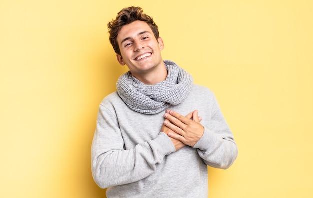 Młody nastolatek chłopiec czuje się romantyczny, szczęśliwy i zakochany, uśmiechając się radośnie i trzymając się za ręce blisko serca