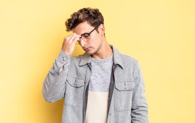 Młody nastolatek chłopiec czuje się zestresowany, nieszczęśliwy i sfrustrowany, dotyka czoła i cierpi na migrenę lub silny ból głowy