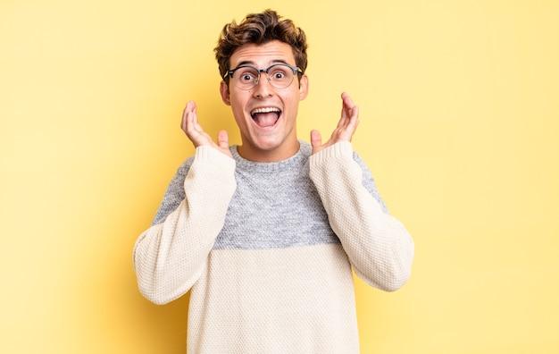Młody nastolatek chłopiec czuje się zszokowany i podekscytowany, śmiejąc się, zdumiony i szczęśliwy z powodu niespodziewanej niespodzianki