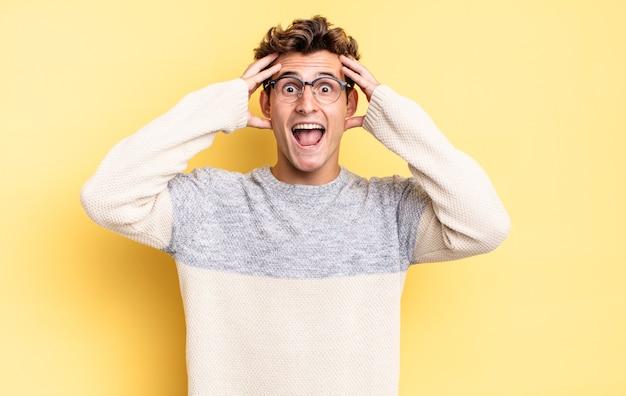 Młody nastolatek chłopiec podnoszący ręce do głowy, z otwartymi ustami, czujący się wyjątkowo szczęśliwy, zaskoczony, podekscytowany i szczęśliwy