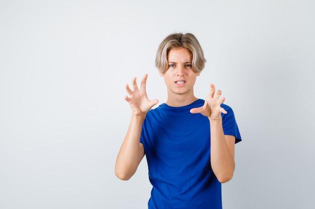 Młody nastolatek chłopiec pokazując pazury imitujący kota w niebieskiej koszulce i wyglądający agresywnie, widok z przodu.