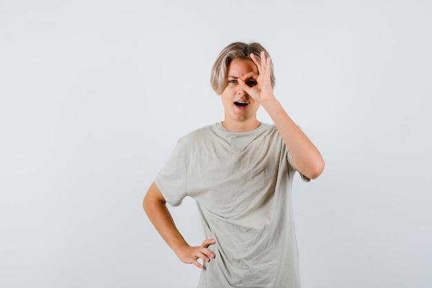 Młody nastolatek chłopiec pokazując znak ok na oko w koszulce i patrząc ciekawy, widok z przodu.