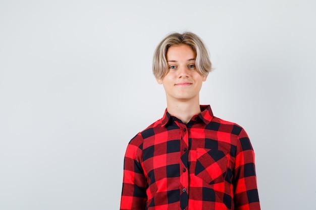 Młody nastolatek chłopiec pozuje stojąc w kraciastej koszuli i wygląda na zadowolonego. przedni widok.