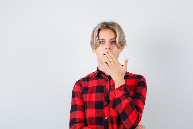 Młody nastolatek chłopiec trzymając rękę na ustach w kraciastej koszuli i patrząc w szoku, widok z przodu.