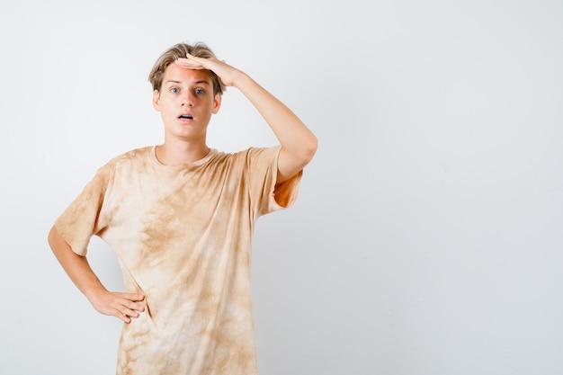 Młody nastolatek chłopiec trzymając rękę nad głową w t-shirt i patrząc zdziwiony. przedni widok.