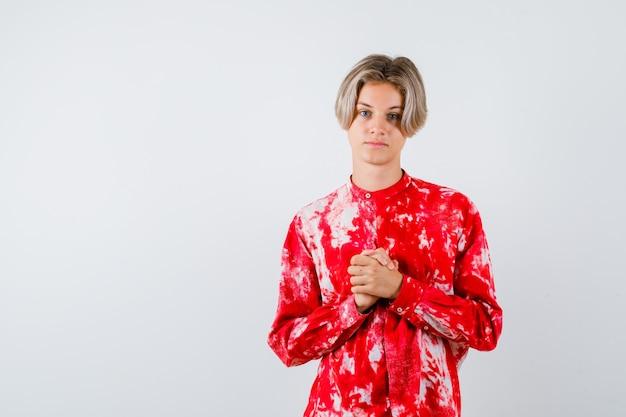 Młody nastolatek chłopiec trzymając splecione ręce nad klatką piersiową w koszuli i patrząc pewnie, widok z przodu.