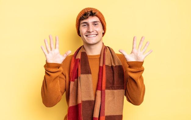 Młody nastolatek chłopiec uśmiechający się i wyglądający przyjaźnie, pokazujący cyfrę dziesiątą lub dziesiątą ręką do przodu, odliczający w dół