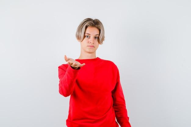 Młody nastolatek chłopiec w czerwonym swetrze rozciągając rękę z przodu i patrząc pewnie, widok z przodu.