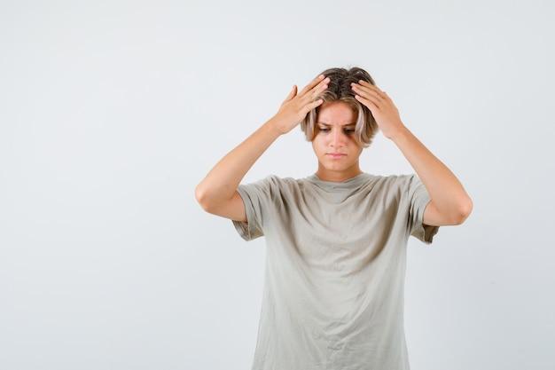 Młody nastolatek chłopiec w koszulce z rękami na głowie