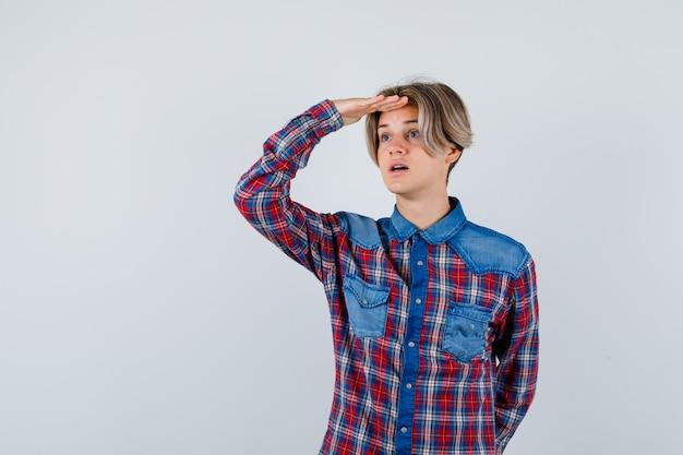 Młody nastolatek chłopiec w kraciastej koszuli patrząc daleko z ręką nad głową i patrząc skupiony, widok z przodu.