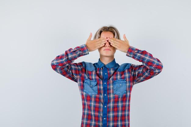 Młody nastolatek chłopiec w kraciastej koszuli, trzymając ręce na oczach i patrząc przestraszony, widok z przodu.