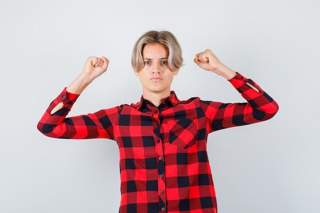 Młody nastolatek chłopiec w kraciastej koszuli, trzymając zaciśnięte pięści i rozwścieczony, widok z przodu.