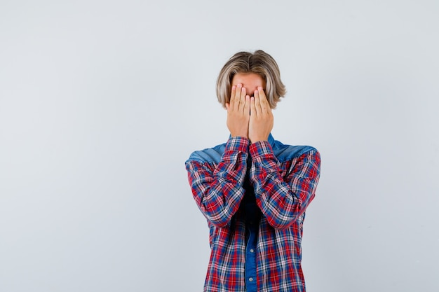 Młody nastolatek chłopiec w kraciastej koszuli zasłaniając twarz rękami i patrząc przygnębiony, widok z przodu.