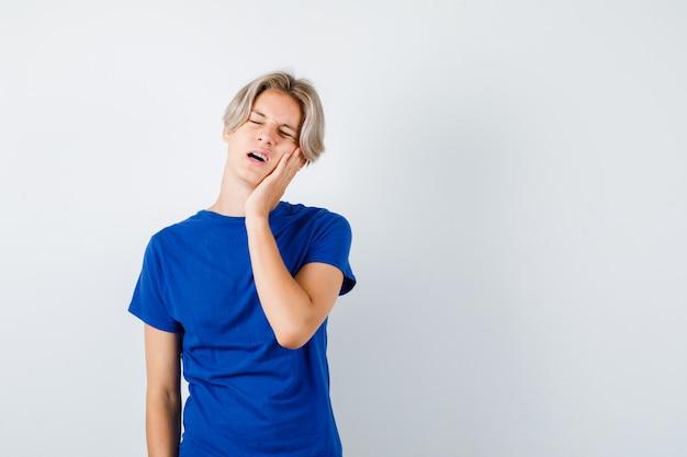 Młody nastolatek chłopiec w niebieskiej koszulce cierpi na okropny ból zęba i wygląda na zaniepokojonego, widok z przodu.
