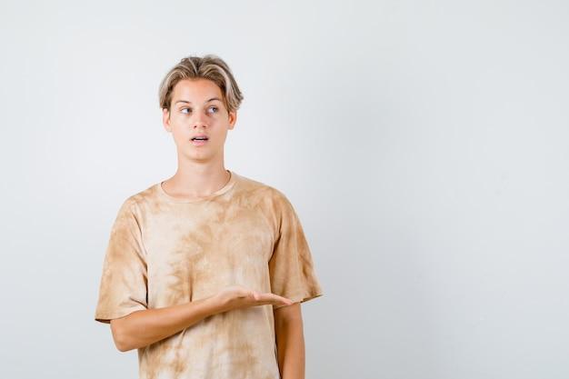 Młody nastolatek chłopiec w t-shirt udaje, że coś pokazuje, przewracając oczami i patrząc skupiony, widok z przodu.