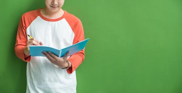 Młody nastolatek chłopiec writing na błękitnym notatniku opiera przy zieleni ścianą