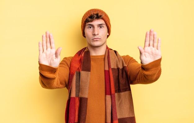"""Młody nastolatek chłopiec wyglądający poważnie, nieszczęśliwy, zły i niezadowolony, zabraniający wejścia lub mówiący """"stop"""" z obiema otwartymi dłońmi"""