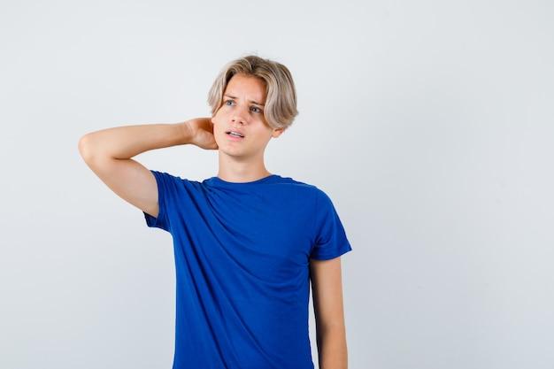 Młody nastolatek chłopiec z ręką za głową, odwracając wzrok w niebieskim t-shirt i patrząc zamyślony, widok z przodu.