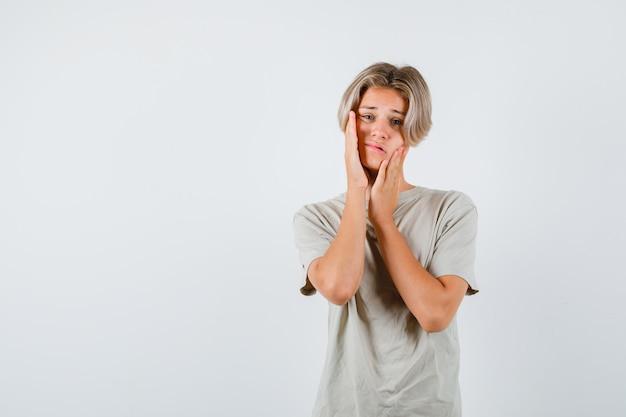 Młody nastolatek cierpiący na ból zęba w koszulce i wyglądający na zdesperowanego