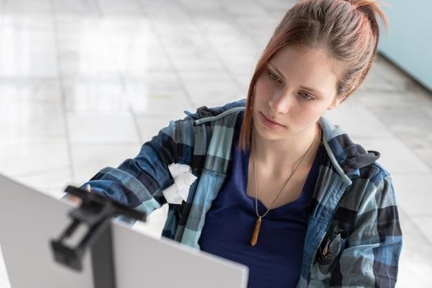 Młody nastolatek kobiety artysta maluje farbami olejnymi siedzi na marmurowej podłoga. białe płótno i sztaluga stoją na podłodze z marmurowych płytek w pokoju o turkusowych i jasnozielonych ścianach.