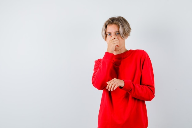 Młody nastolatek, który czuje coś okropnego, szczypie nos w czerwonym swetrze i wygląda na zdegustowanego, widok z przodu.