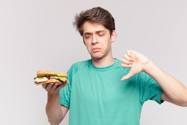 Młody nastolatek mężczyzna smutny wyraz i trzymający kanapkę