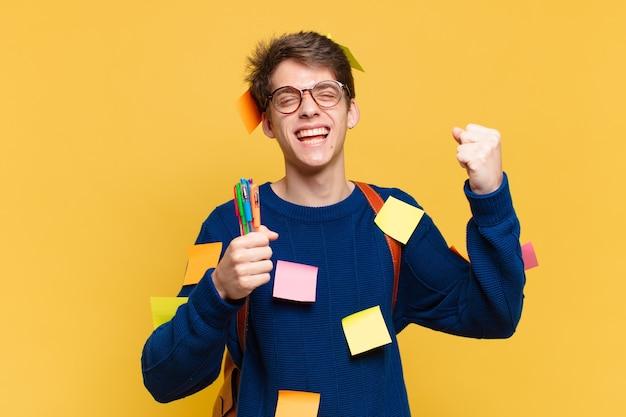 Młody nastolatek mężczyzna świętuje sukcesy zwycięstwa. koncepcja studenta uniwersytetu